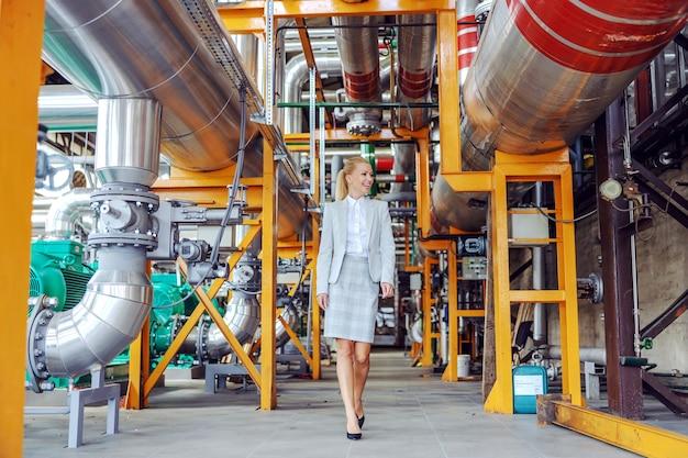 笑顔の金髪の女性発電所の所有者が歩き回って機械をチェックしています。