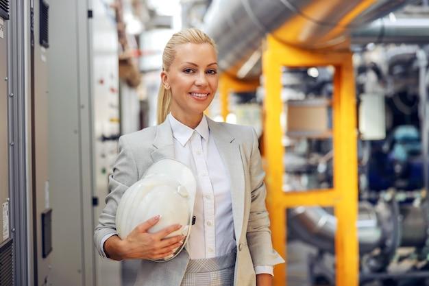 発電所に立っている間、手に保護ヘルメットを保持している金髪の女性監督者の笑顔。