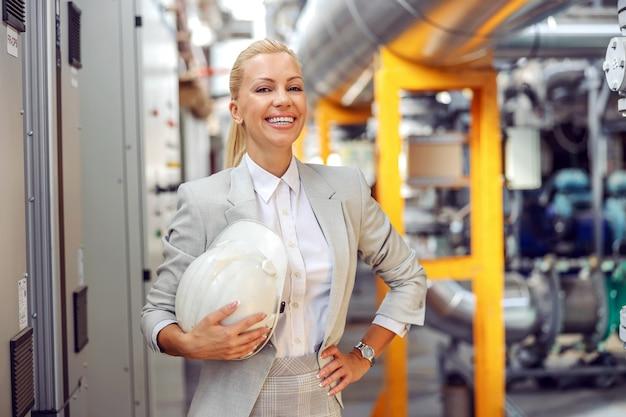 発電所に立っている間、手に保護ヘルメットを保持している金髪の女性監督者の笑顔