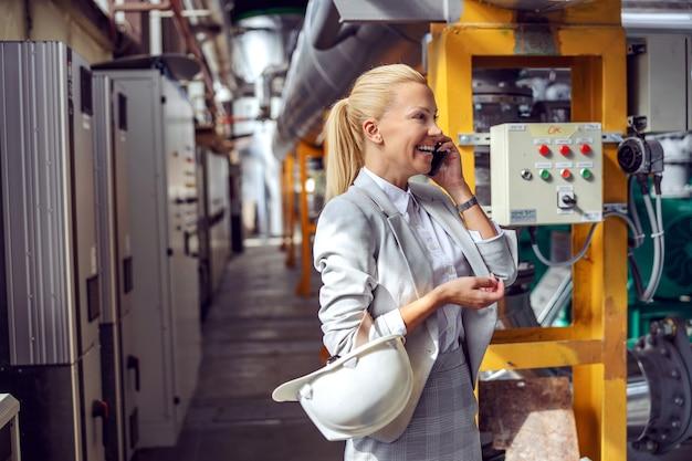 Улыбающаяся белокурая женщина-руководитель в формальной одежде держит защитный шлем вокруг руки и разговаривает по телефону со своим боссом, стоя на электростанции.