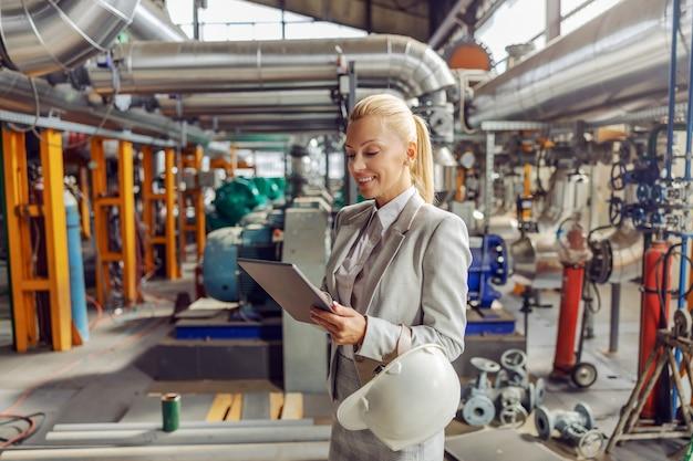 난방 공장에 서 태블릿을 사용 하여 금발 친화적 인 여성 감독자 미소.