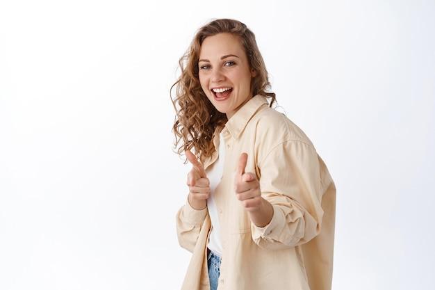 Sorridente ragazza bionda rallegra, lodando o scegliendo te, puntando il dito davanti e guardando felice, in piedi sul muro bianco