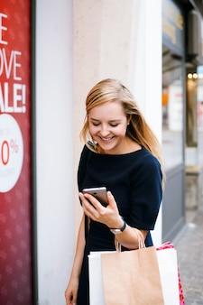 Улыбающаяся блондинка в черном платье смотрит в мобильный телефон и несет сумки после покупок