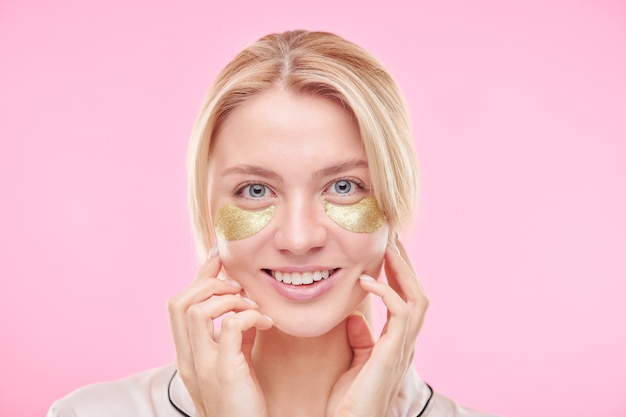 Smiling blond girl with golden revitalising under-eye patches touching her face while standing against pink wall