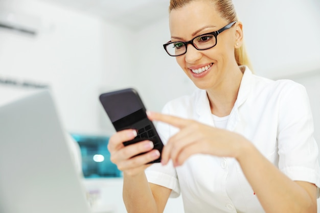 Smiling blond lab assistant with eyeglasses using smart phone on a break while sitting in laboratory.