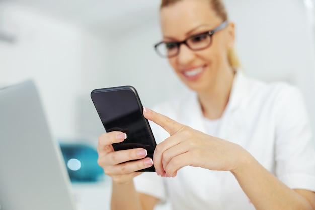 研究室に座っている間、休憩中にスマートフォンを使用して眼鏡で金髪の研究室助手を笑顔。電話に選択的に焦点を当てます。
