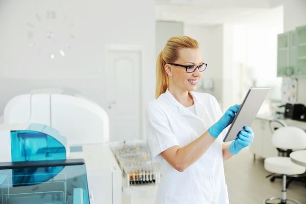 タブレットを押しながらテスト結果を入力するゴム手袋でブロンドのラボアシスタントを笑顔にします。