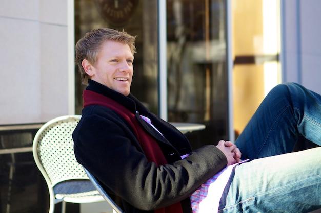 通りの椅子に座っている黒いコートを着た金髪の男性の笑顔