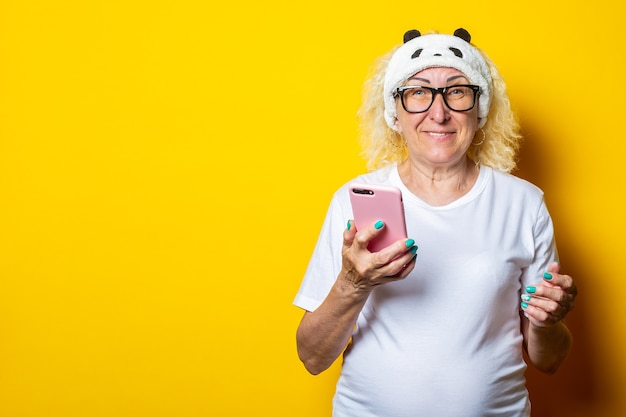 Smiling blond old woman in sleep mask holding phone