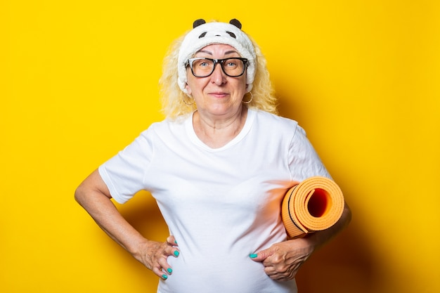 Smiling blond old woman wearing sleep mask holding yoga mat