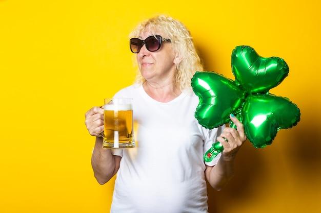 맥주 한 잔으로 금발 할머니를 웃고 클로버 잎의 풍선 공기 풍선을 들고