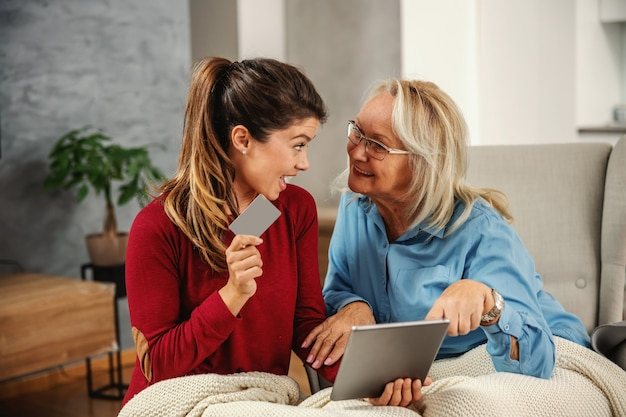 椅子に座ってオンラインショッピングのためのタブレットを見て笑顔の金髪の年配の女性。
