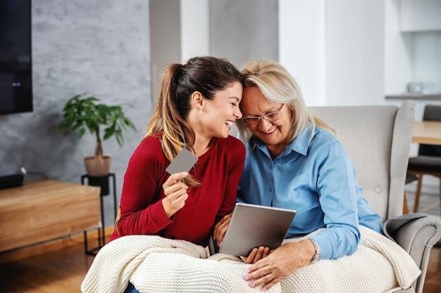 椅子に座ってタブレットを見て笑顔の金髪の年配の女性。彼女の娘は彼女の隣に座って、タブレットとクレジットカードを持っています。彼らはオンラインで買い物をしようとしています。