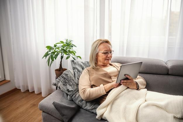 소파에 앉아서 온라인 조언을 위해 태블릿을 사용하여 웃는 금발 고위 여자.