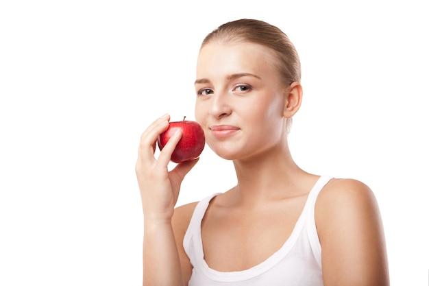 Улыбающаяся блондинка ест красное яблоко на белом