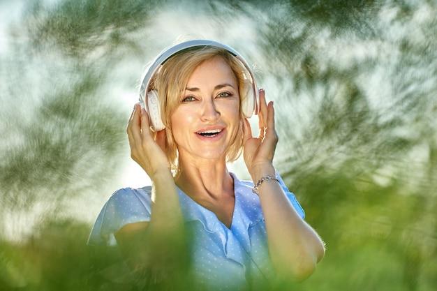 무선 헤드폰을 끼고 웃고 있는 금발의 여자가 공원을 산책한다