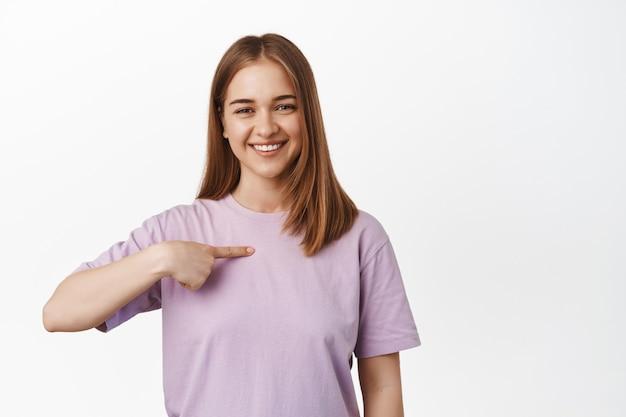 笑顔の金髪女性が自分を指さし、ボランティアをし、参加を求め、自慢し、彼女の業績について話し、白い壁の上に立っています。