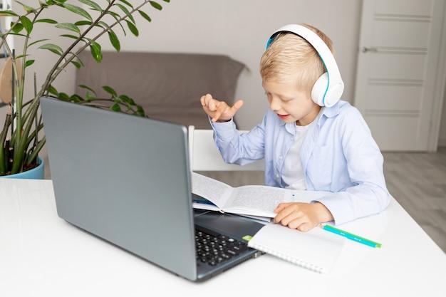 웃는 금발 소년은 집에서 전자 거리 학습 중 노트북을 통해 화상 통화를하고, 개념은 다시 학교로