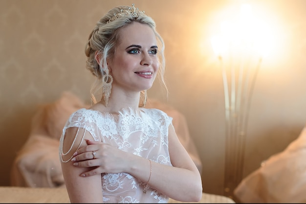 Smiling blonde bride in a hotel room is standing in the boudoir