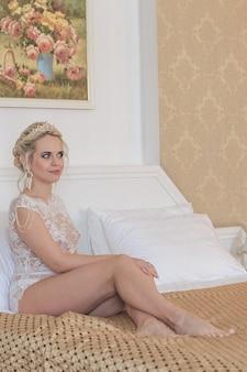 ホテルの部屋の透明な私室で笑顔の金髪の花嫁はベッドの上に横たわっています。