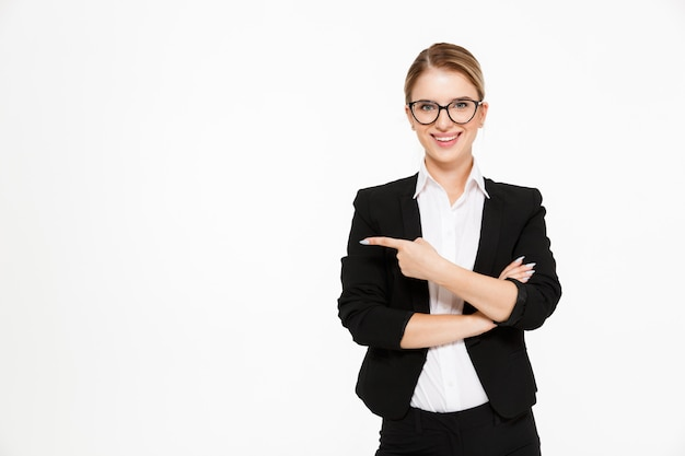 Smiling blonde business woman in eyeglasses pointing away