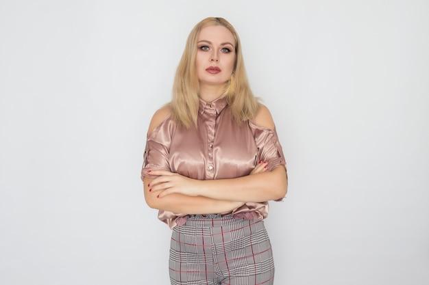 Улыбающаяся блондинка бизнес-леди в розовой блузке на белом фоне