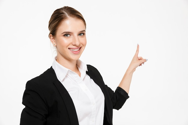 Smiling blonde business woman pointing back