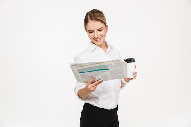 Smiling blonde business woman reading newspaper while holding cup of coffee over white wall