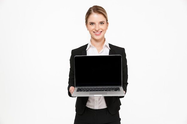 Smiling blonde business woman showing blank laptop computer screen and  over white wall
