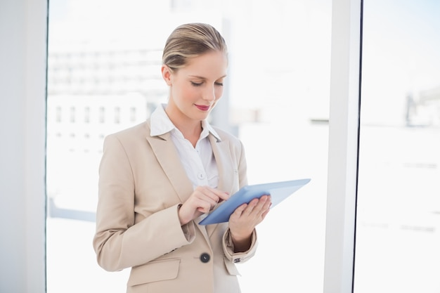 Smiling blonde businesswoman using tablet pc
