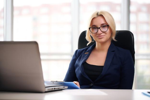 オフィスでラップトップを使用してメガネで金髪の実業家を笑顔。