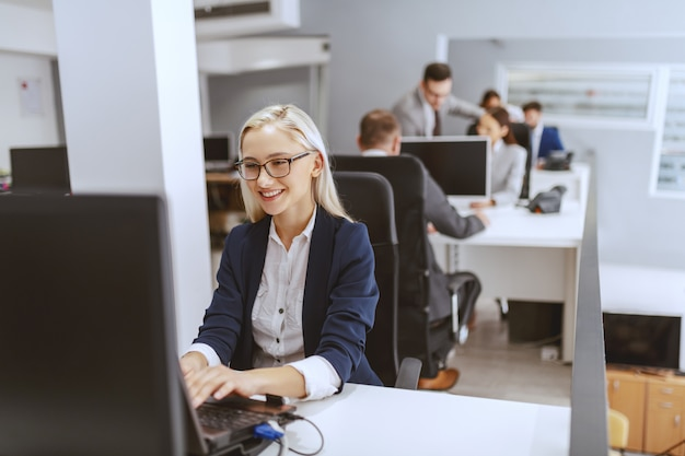 Smiling blonde caucasian businesswoman sitting at her workplace and using computer. hands on keyboard.