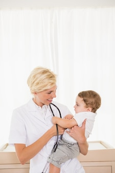 Улыбается блондинка врач и ребенок
