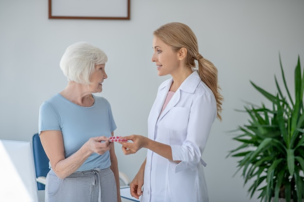 Улыбающаяся блондинка-врач дает женщине волдырь с пилсами
