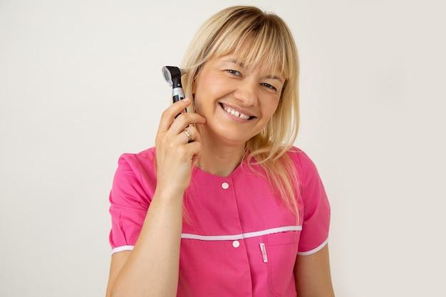Улыбающаяся блондинка-врач в ярко-розовой медицинской форме показывает, что отоскопическое обследование - безболезненная и приятная процедура. медицинская страховка. профилактические осмотры. медицинское оборудование. образ жизни.