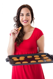 白い背景にホットなクッキーを食べるブロンドの笑顔