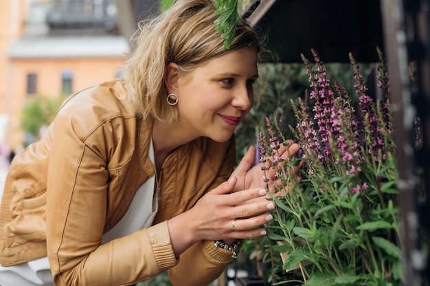 Улыбающаяся блондинка наслаждается ароматом цветов, выставленных на уличной витрине. работа флориста. ароматерапия. лекарственные травы и растения. кусочек природы в городе.