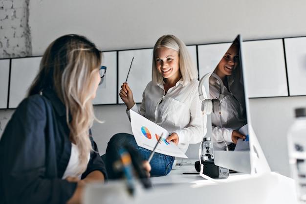 Responsabile femminile biondo sorridente che tiene infografica e matita, mentre era seduto sul tavolo. ritratto dell'interno di due donne che lavorano con il computer in ufficio.