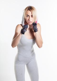 Улыбающаяся блондинка подходит женщина в спортивной одежде боксерский пучок в камеру