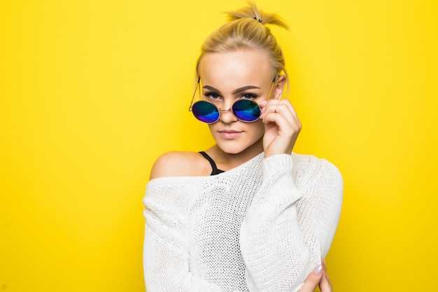 Smiling blonde girl in modern white sweater in brilliant blue sunglasses is posing on yellow