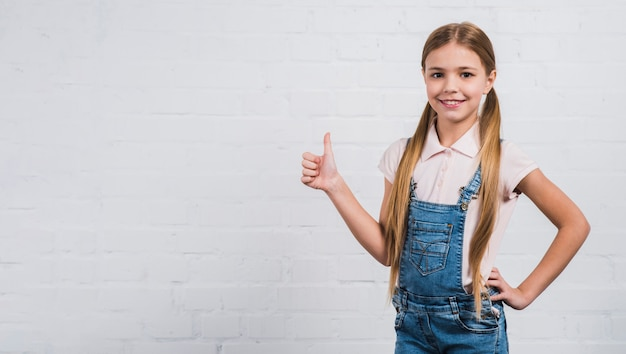 Smiling blonde girl showing thumb up sign standing against white brick wall