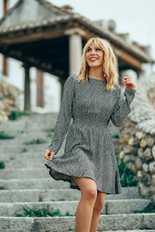 Smiling blonde girl wearing dress dancing outdoors.