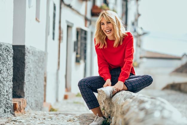 Smiling blonde girl with red shirt enjoying life outdoors.