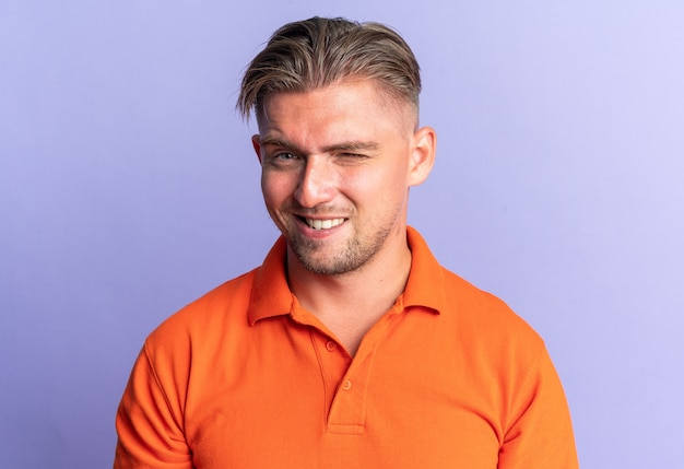 Smiling blonde handsome man blinks his eye  isolated on purple wall with copy space