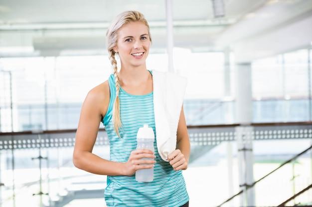 Smiling blonde holding bottle at leisure center