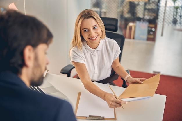 男からテーブルを横切って座っている間鉛筆とドキュメントを保持している笑顔のブロンドの女性