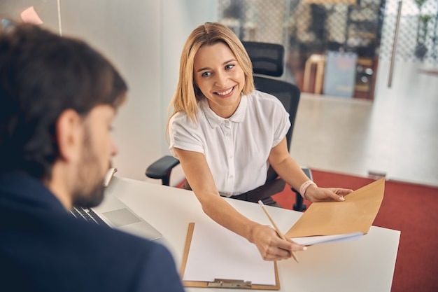 Smiling blonde lady holding pencil and documents while sitting across the table from man