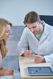 Smiling blonde lady scrutinizing a deaf aid in the hands of a young cute male doctor