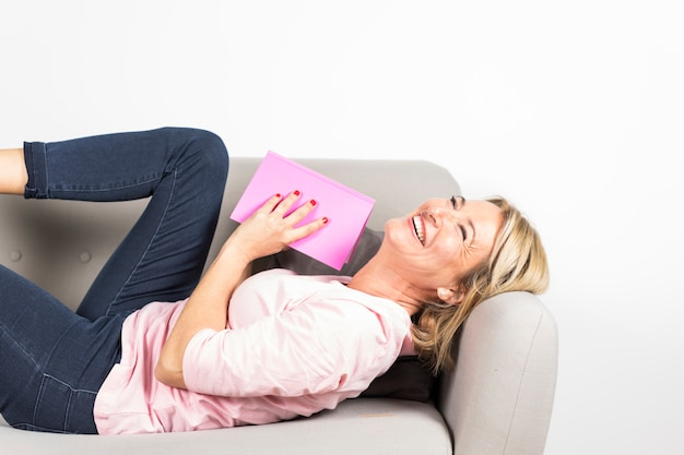 Smiling blonde mature woman lying on sofa holding pink cover book against white backdrop
