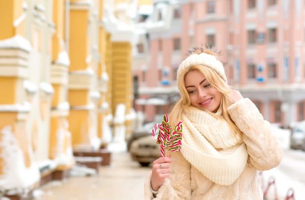 暖かい帽子とおいしいクリスマスのお菓子を保持しているコートで金髪モデルの笑顔